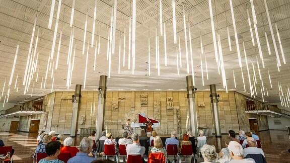Der Cellist Daniel Müller-Schott und die Cembalistin Irina Zahharenkova beim Konzert der MDR-Musiksommer Sonderausgabe am 26. Juli 2020 im Kultur- und Kongresszentrum Gera. Über der Bühne hängen längliche Lampen.