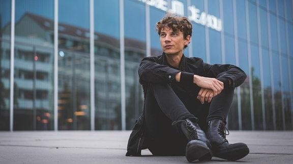 Francesco Tristano sitzend vor dem Bauhaus Museum Dessau