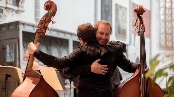 Zwei Kontrabassisten der Kammersymphonie Leipzig umarmen sich nach ihrem Konzert beim MDR-Musiksommer in der Kulturkirche in Weißensee.