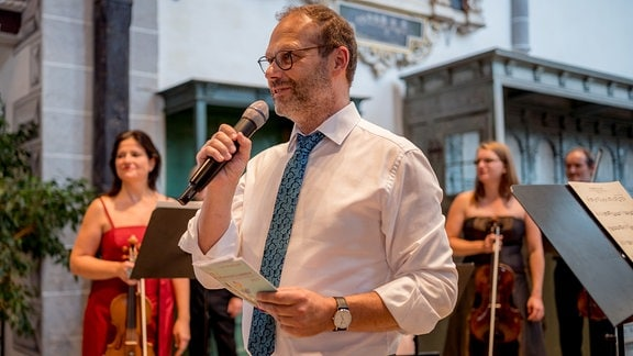 Oliver Jueterbock mit Mikrofon beim MDR-Musiksommer in der Kulturkirche in Weißensee.