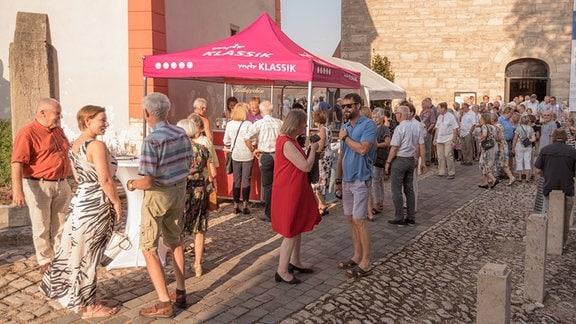 Konzertgäste in der Pause vor der Kulturkirche in Weißensee beim MDR-Musiksommer.