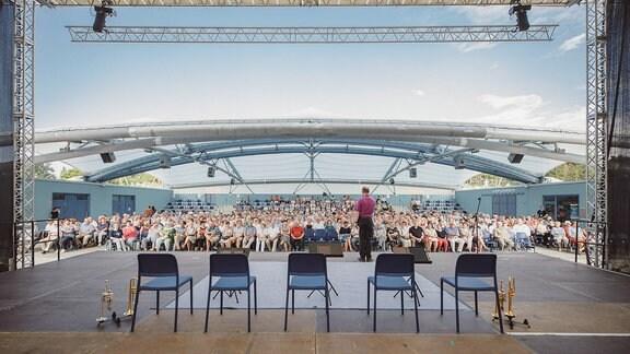 Blick von der Seestern-Panoramabühne Zeulenroda ins Publikum. Auf der Bühne stehen fünf Stühle und Blechblasinstrumente.