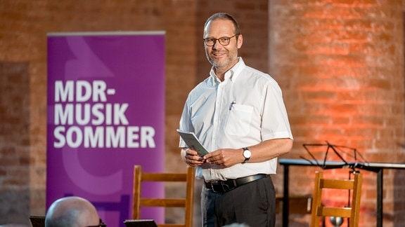 Oliver Jueterbock, Manager des MDR-Musiksommers, steht vor dem Publikum in der Jerichower Klosterkirche und eröffnet das Konzert.
