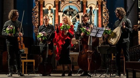 Simone Kermes und ihr Kammermusikensemble verbeugen sich mit Blumen in den Händen nach dem MDR-Musiksommer-Konzert in Tangermünde.
