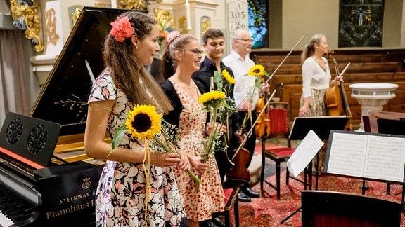 Drei Jugendliche stehen nach einem Konzert beim MDR-Musiksommer mit Blumen auf der Bühne.