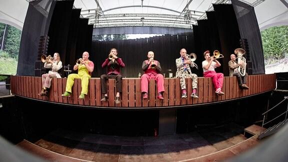 Das Blechblas-Ensemble Mnozil Brass sitzt auf dem vorderen Bühnenrand im Naturtheater Bad Elster beim MDR MUSIKSOMMER