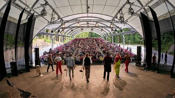 Blick von der Bühne in den Zuschauerraum des Naturtheaters Bad Elster beim MDR MUSIKSOMMER. Auf der Bühne steht das Blechblas-Ensemble Mnozil Brass mit Blumen.