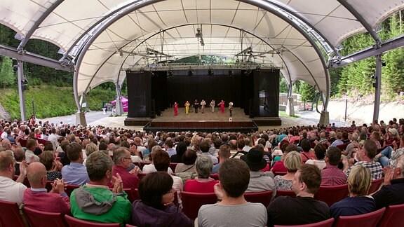 Blick über die Zuschauerreihen auf das Blechblas-Ensemble Mnozil Brass auf der Bühne im Naturtheater Bad Elster beim MDR MUSIKSOMMER.