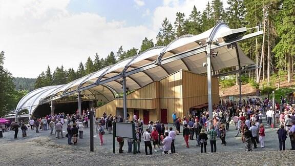 Besucher stehen vor dem Naturtheater Bad Elster beim MDR MUSIKSOMMER, dahinter ist der Wald zu sehen.