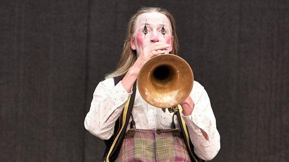 Ein Mitglied des Blechblas-Ensembles Mnozil Brass hat sich als trauriger Clown verkleidet und sitzt auf der Bühne im Naturtheater Bad Elster beim MDR MUSIKSOMMER.