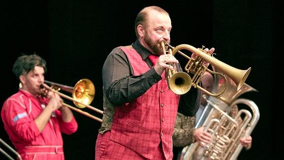 Drei Musiker des Blechblas-Ensembles Mnozil Brass im Naturtheater Bad Elster beim MDR MUSIKSOMMER. Einer spielt zwei Instrumente.
