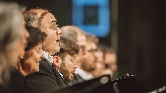 Der MDR-Rundfunkchor singt zum Eröffnungskonzert des MDR-Musiksommers 2017 im Erfurter Dom. Seitenansicht einer Reihe mit Sängerinnen und Sängern.