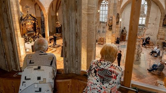 Zwei Menschen schauen von der Empore des Freiburger Doms beim Konzert des MDR-Musiksommers 2021 zu.