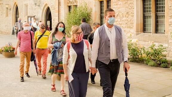 Konzertgäste in bunter Sommerkleidung kommen aus dem Erfurter Augustinerkloster.