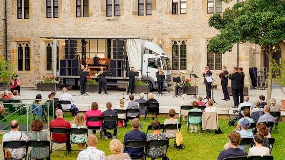 Cameron Carpenter am Orgelspieltisch seines Orgeltrucks, davor das Blechbläserensemble. Im Vordergrund sitzen Konzertbesucher in sommerlich bunter Kleidung auf Klappstühlen.