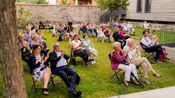 Konzertgäste in bunter Sommerkleidung sitzen auf Klappstühlen und applaudieren beim Eröffnungskonzert der MDR-Musiksommer Sonderausgabe in Erfurt.