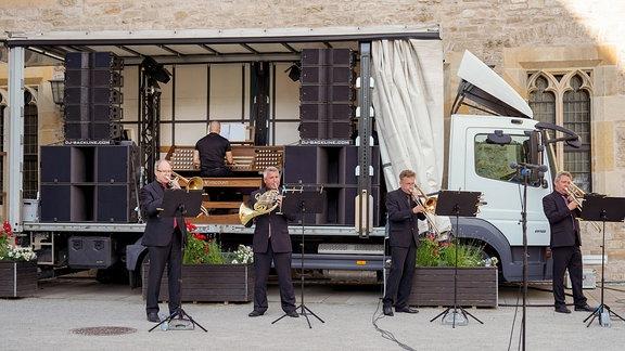 Gemeinsam mit Cameron Carpenter, der am Orgelspieltisch auf einem LKW mit großen Boxen sitzt, musizieren Blechbläser beim Eröffnungskonzert der MDR-Musiksommer Sonderausgabe in Erfurt