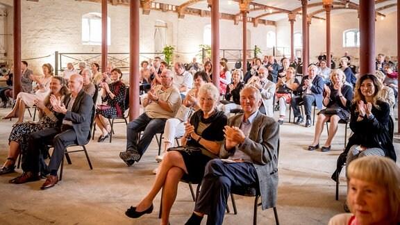 Das Publikum sitzt mit Abstand in Zweiergrüppchen und applaudiert beim Konzert der MDR-Musiksommer Sonderausgabe im Konzertstall auf dem Gutshof Seggerde.