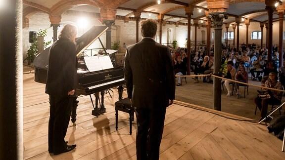 Bariton Christian Gerhaher und Pianist Gerold Huber stehen auf der Bühne beim Konzert der MDR-Musiksommer Sonderausgabe im Konzertstall auf dem Gutshof Seggerde, Publikum applaudiert.