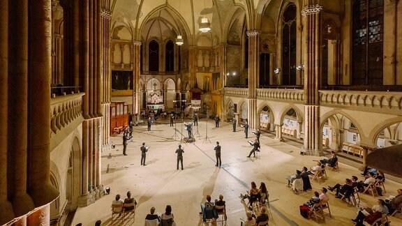 Aufnahme aus der Vogelperspektive: Zu sehen sind Sängerinnen und Sänger eines Chores, sie stehen kreisförmig, in der Mitte ein Dirigent. Sie singen vor Publikum, das mit dem nötigen Mindestabstand in der Kirche Platz genommen hat.