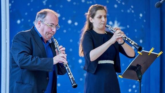 Eine Oboist und eine Oboistin aus dem MDR-Sinfonieorchester musizieren vor nachtblauem Hintergrund im Pavillon der Stadthalle Görlitz