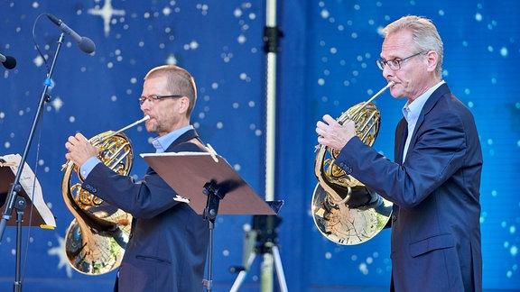 Zwei Hornisten des MDR-Sinfonieorchesters vor nachtblauem Hintergrund im Pavillon der Stadthalle Chemnitz