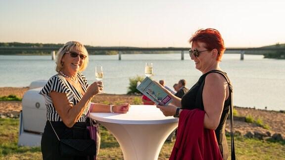 Zwei Konzertbesucherinnen im Abendlicht mit einem Glas Sekt in der Hand