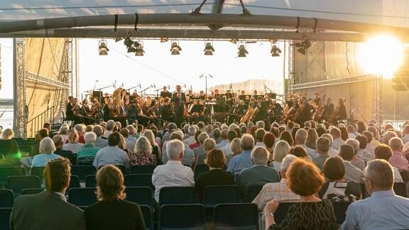 MDR-Musiksommer-Manager Oliver Jueterbock begrüßt das Publikum in Zeulenroda, im Hintergrund das MDR-Sinfonieorchester