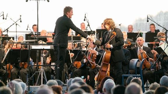 Dirigent Karsten Januschke schüttelt Solocellist Rodin-George Moldovan die Hand, im Hintergrund das MDR-Sinfonieorchester