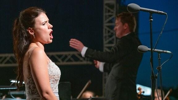 Sopranistin Katharina Ruckgaber, im Hintergrund Dirigent Karsten Januschke