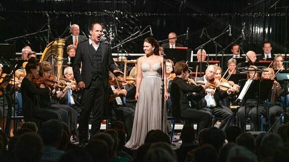 Die Solisten Katharina Ruckgaber (Sopran) und Mathias Hausmann (Bariton) vor dem MDR-Sinfonieorchester