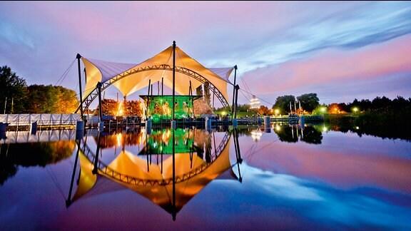 Die Seebühne im Elbauenpark in Magdeburg im Dämmerlicht, festlich erleuchtet.