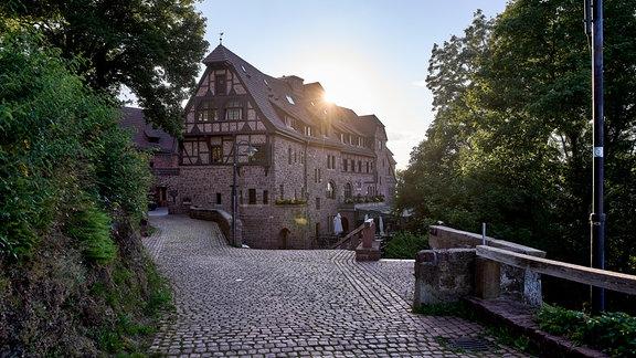 Aufgang zur Wartburg, Blick auf Hotel, hinter dessen Dach die Sonne untergeht