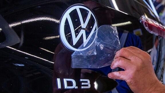 Ein Mitarbeiter entfernt eine Schutzfolie vom VW-Logo