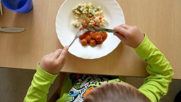 Ein Kind isst ein warmes Essen in der Kita