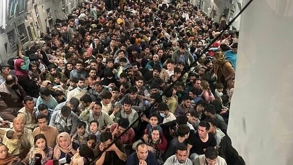 Eine große Menschengruppe in einem US-Militärflugzeug