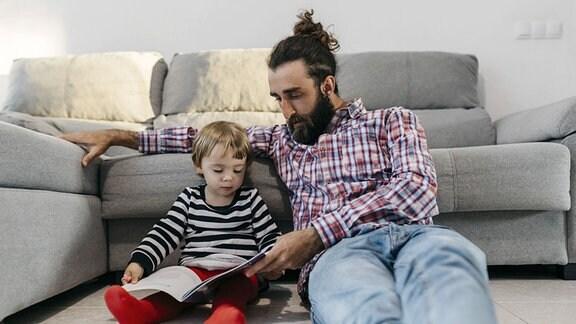 Ein Vater sitzt mit seiner kleinen Tochter im Wohnzimmer vor dem Sofa und blättert mit ihr in einem Buch.