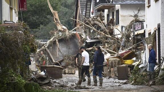 Ein umgestürzter Lkw und Baumäste blockiert eine Straßen, davor räumen Menschen auf/Gemeinde Altenahr im Kreis Ahrweiler in Rheinland-Pfalz