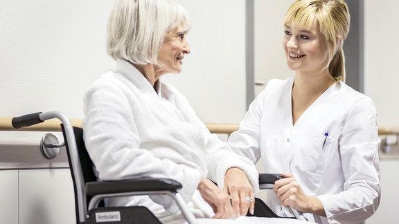 Pflegerin spricht mit Seniorin im Rollstuhl