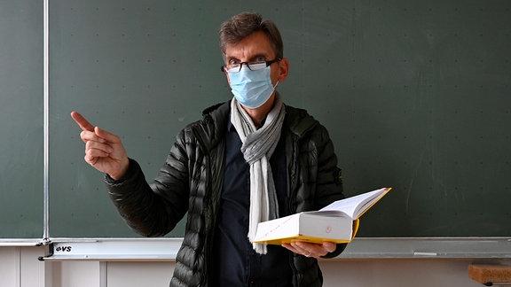 Lehrer mit dicker Winterjacke, Schal und Mundschutzmaske
