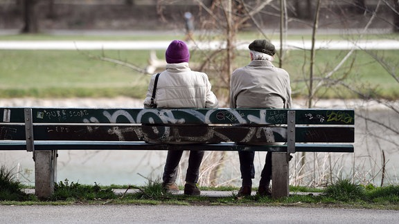 Rentner -Mann und Frau, sitzen auf einer Bank