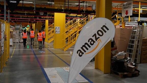 Mitarbeiter in der Werkhalle mit Amazon Logo