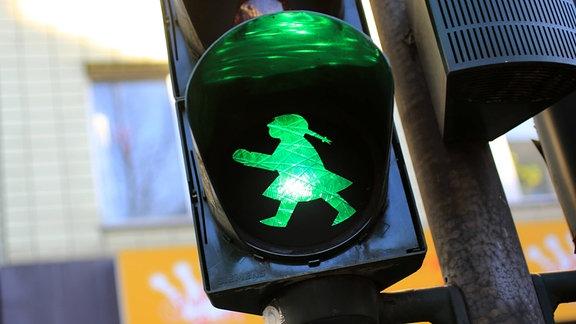 Ein grünes Ampelmädchen auf einer Ampel.