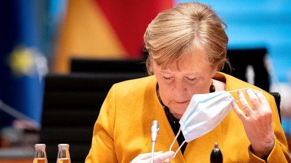 Kanzlerin Angela Merkel in gelber Jacke nimmt ihren Mundschutz ab, auf der wöchentlichen Sitzung des Bundeskabinetts im März 2021