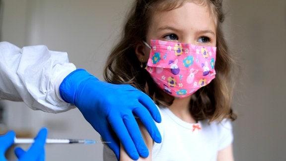 Ein Mädchen mit einer rosafarbenen Maske bekommt von einem Arzt eine Spritze
