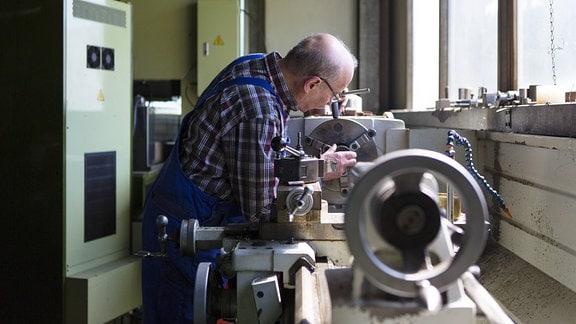 Ein älterer Herr arbeitet 2014 in einem mittelständischen Unternehmen für Maschinenbauteile