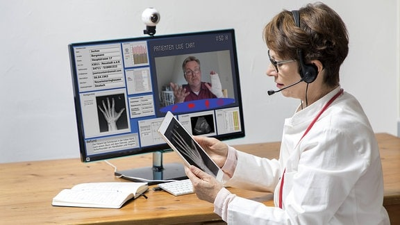 Symbolfoto zur Telemedizin, Ärztin in einer Praxis, kommuniziert mit dem Patienten über eine Webcam
