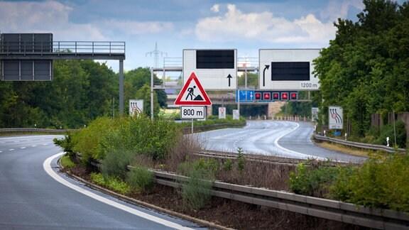 Vollgesperrte sechsstreifige Autobahn ohne Fahrzeuge mit Schilderbrücke, Hinweis- und Baustellenschildern