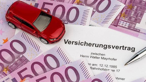 Spielzeugauto auf Geldscheinen und Versicherungsvertrag