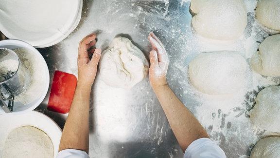 Ein Bäcker knetet Teig